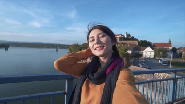 Portrait of charming girl on the background of beautiful landscape. Young fashionable woman selfie on walk. Smiling lady in stylish clothes taking selfie. Concept of recreation and tourism