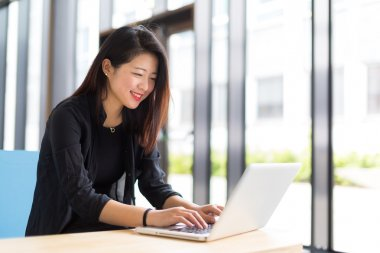 Asian college student sitting with a laptop smiling