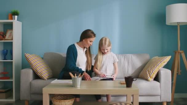 Mutter und Mädchen schließen Freundschaft beim gemeinsamen Lesen