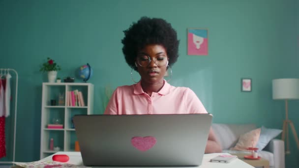 A nő laptopon dolgozik, és a kamerát nézi.
