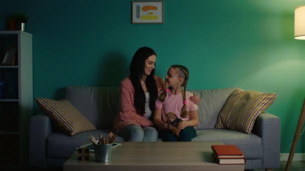 Portrét malé dívky a mladé matky sedí na pohovce doma