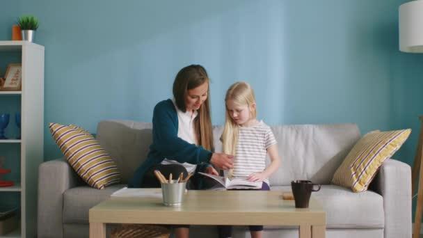 Mutter und Tochter suchen Bilder im Buch