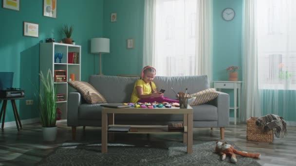 A kislány otthon okostelefont használ.