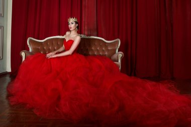 Beautiful girl in long red dress and in royal crown