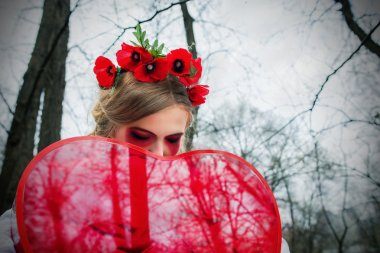 Young blonde girl in national ukrainian blouse and with wreath of poppies and big red heart in her hands crying bloody tears in the cemetery