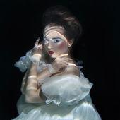 mladá dívka v dlouhé bílé luxusní šaty pod vodou na černém pozadí