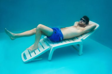 portrait of the young man in the sun glasses laying on the sunbed underwater in the swimming pool