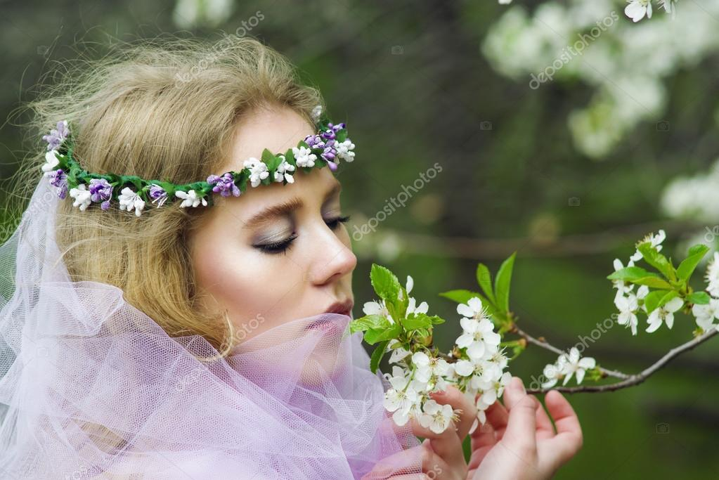 beautiful young blonde girl in blooming trees in spring