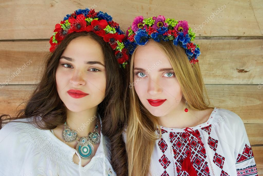 Two young beautiful girls with long hair in Ukrainian blouses and in a wreathes in outdoor