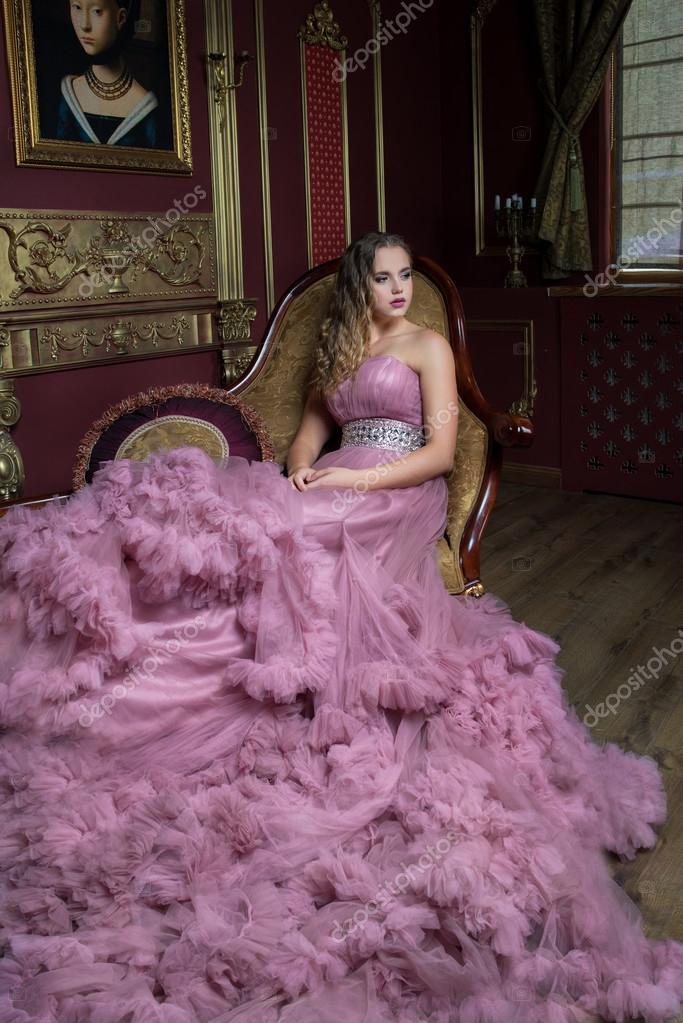 6ba178b4f2 Ritratto di giovane bella ragazza in abito lungo rosa seduta sul ...