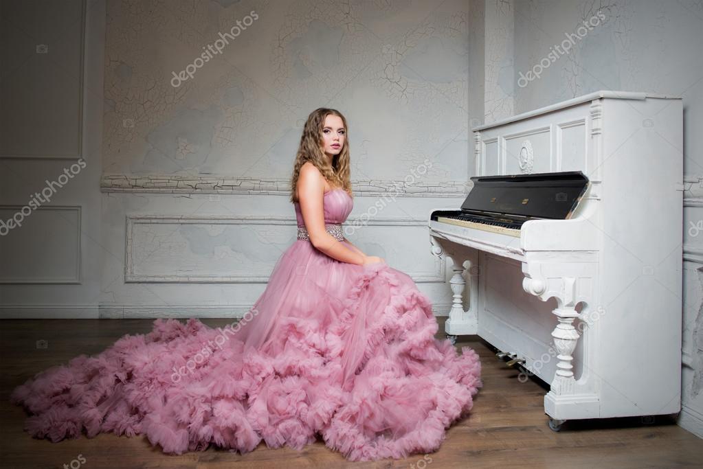 4211d08912 Ritratto di giovane bella ragazza in abito lungo rosa vicino al ...