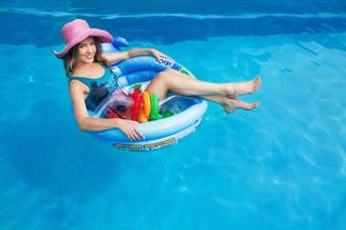 beautiful girl floating in the swimming circle in the pool in summer