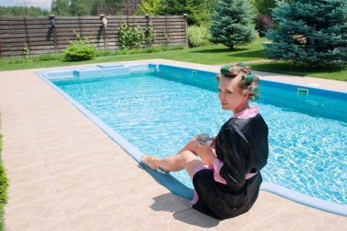 young girl in a bathrobe and curlers  drinking coffee near  the swimming pool in summer