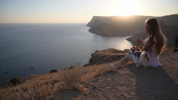 poslušnost životní styl psa psí trénink od mladé ženy sedí se dvěma mazlíčky čivava na krásném mořském horském pobřeží na teplém letním západu slunce
