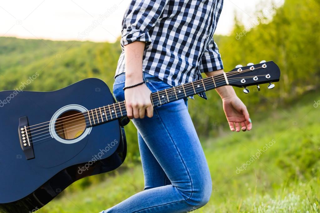 Girl walking in the field with a guitar in hand