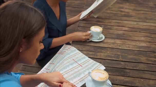 Woman looking for Job in a Newspaper while having coffee