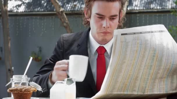 businessman reading newspaper in cafe