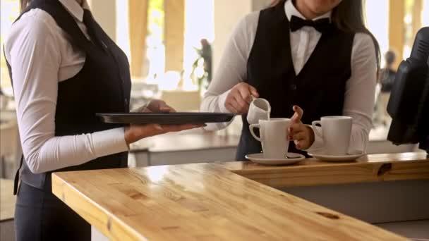 číšník připravuje hrnečky pro servírování zákazníkům