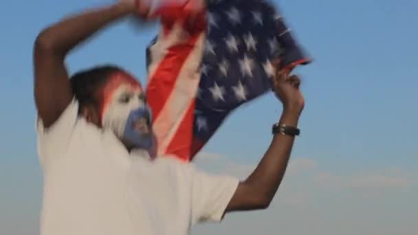 sportovní fanoušek oslavující s americkou vlajkou a malování na obličej