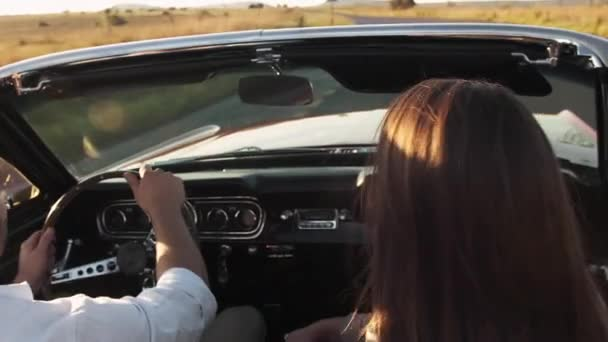 Couple driving cabriolet car on empty road