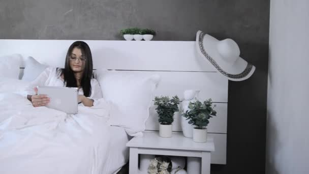 business woman using tablet computer in bed