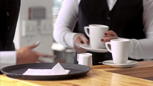 waiter pouring preparing coffee mugs