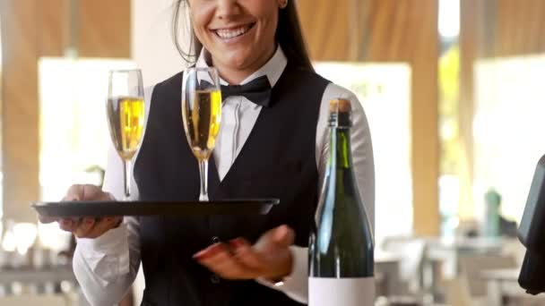 Medium shot of happy staff waiter smiling, while holding tray with champagne glasses after it has being pored.