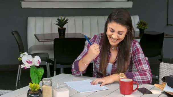 student girl writing notes in cafe