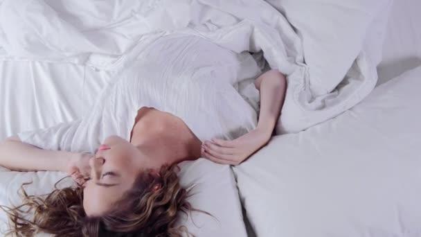 spí v posteli, probuzení a usmívající se žena
