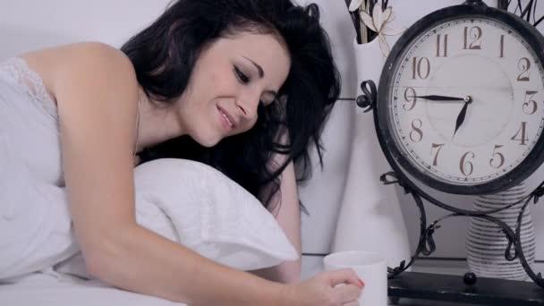 žena v bílé posteli s kávou