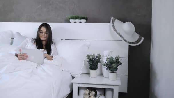 podnikání žena pomocí tabletového počítače v posteli