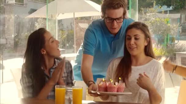 přátel slavit narozeniny s košíčky v kavárně