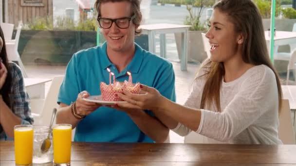 přátel slavit narozeniny s košíčky a svíčky