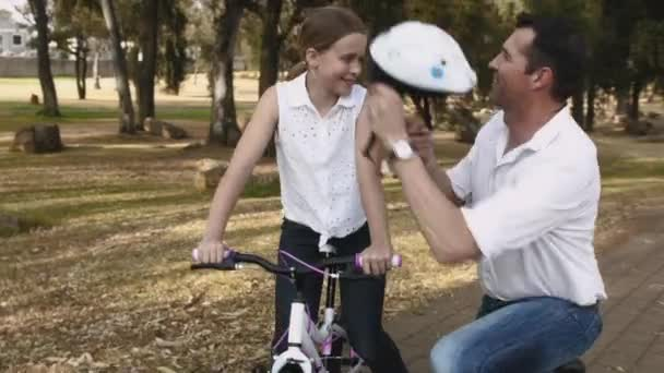 Father clipping helmet on daughters head