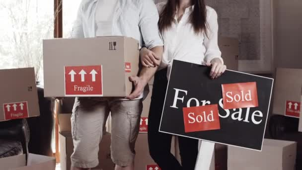 couple with there boxes and for sale sign board