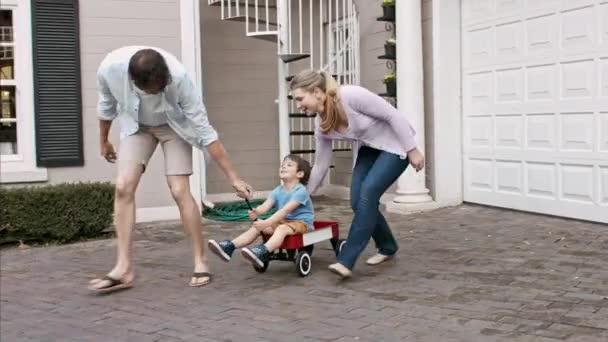 otec a matka tahání syna ve voze