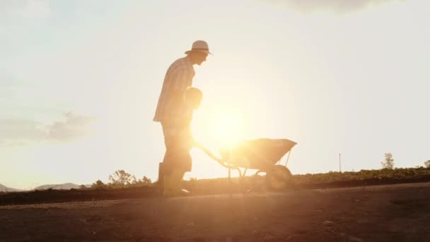 Father Helping Son Push Wheelbarrow