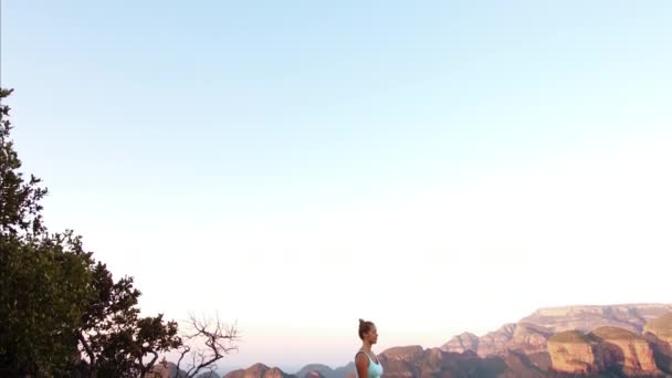 woman practicing meditation on the top of mountain