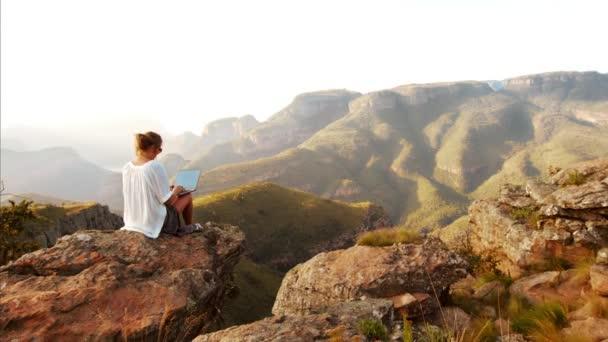 žena pracující na notebooku v horách