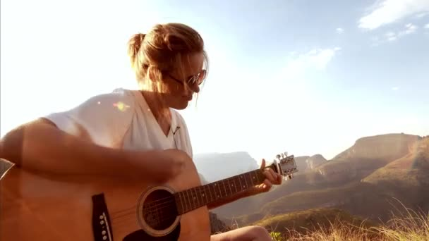 Woman playing guitar on the top of a mountain.