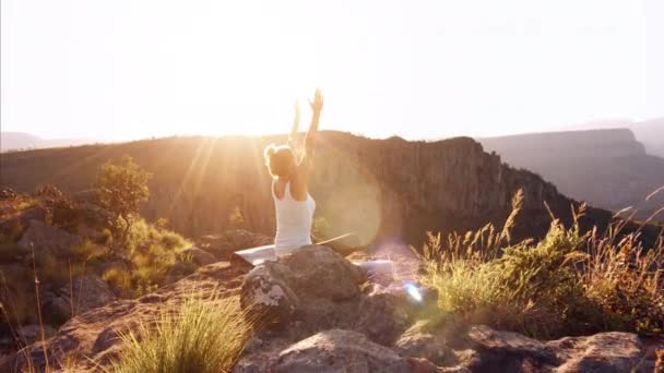 woman practicing yoga on the top of mountain