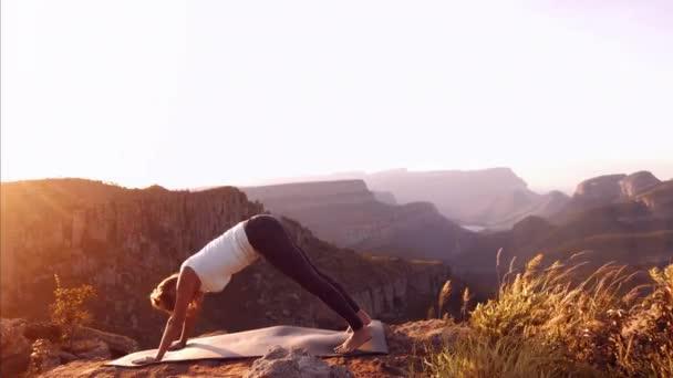 žena cvičí jógu na vrcholu hory