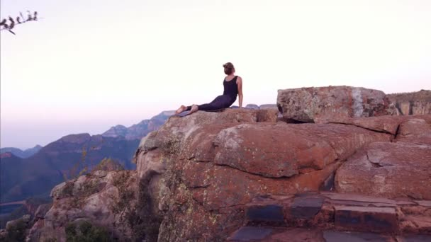 Woman yoga practitioner on top of a mountain