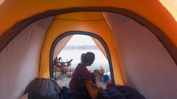 traveler playing guitar in camping tent