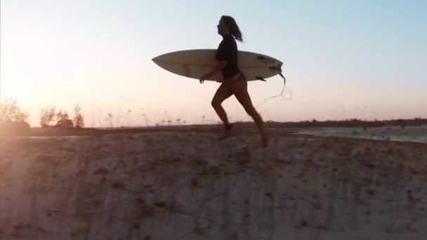 surfařka běžící na pláži