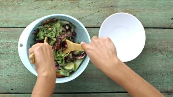 hands tossing, and dishing salad