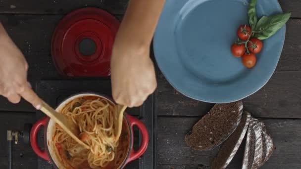 preparing spaghetti to serve on plate
