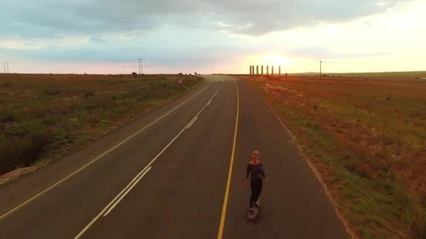 4 k magické dron záběry žena cestovatele, dlouhé strávník na koni její dlouhá deska po silnici při západu slunce