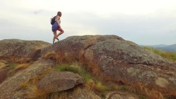 4 k Drone záběry mladých nezávislých žen tramp s batohem dosahující nahoře na vrcholu hory šíření zvednuté ruce. Úspěch, inspirace, zdarma, krásné scenérie, vyhrál, motivace. 4k