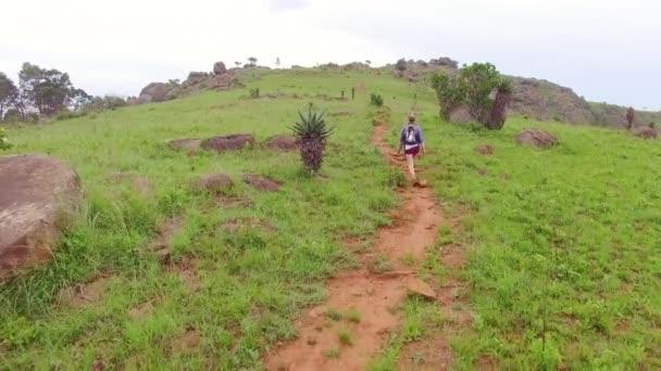 4 k Drone záběry mladých nezávislých žen tramp s batohem chůzi na cestě na vrcholu hory cestování v afrických